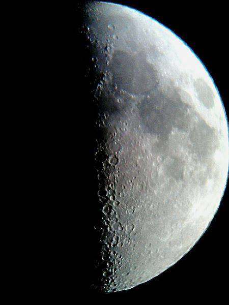 Photograph of the Moon showing the terminator line and craters.