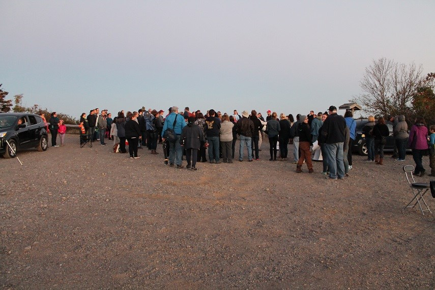group of people waiting to look through telescopes