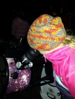 Photo of girl looking through telescope at an SJAC Outreach Event