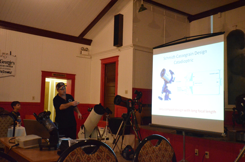 Photograph of Paul Owen pointing out different types of telescopes at workshop.
