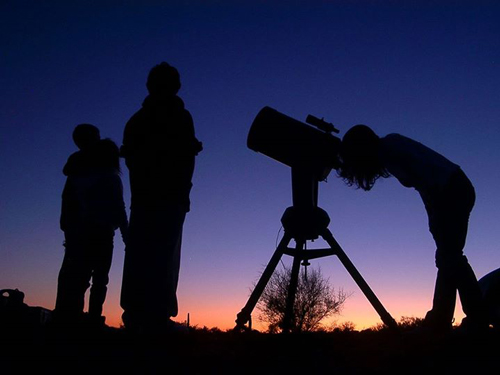 Photo of people looking through a telescope.
