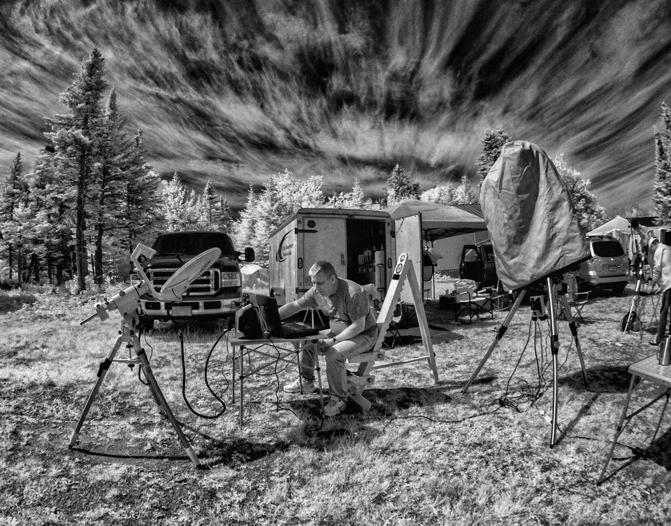 A black & white infrared photo of astronomer Mike Powell listening to the Sun with his homemade IBRT (Itty Bitty Radio Telescope).