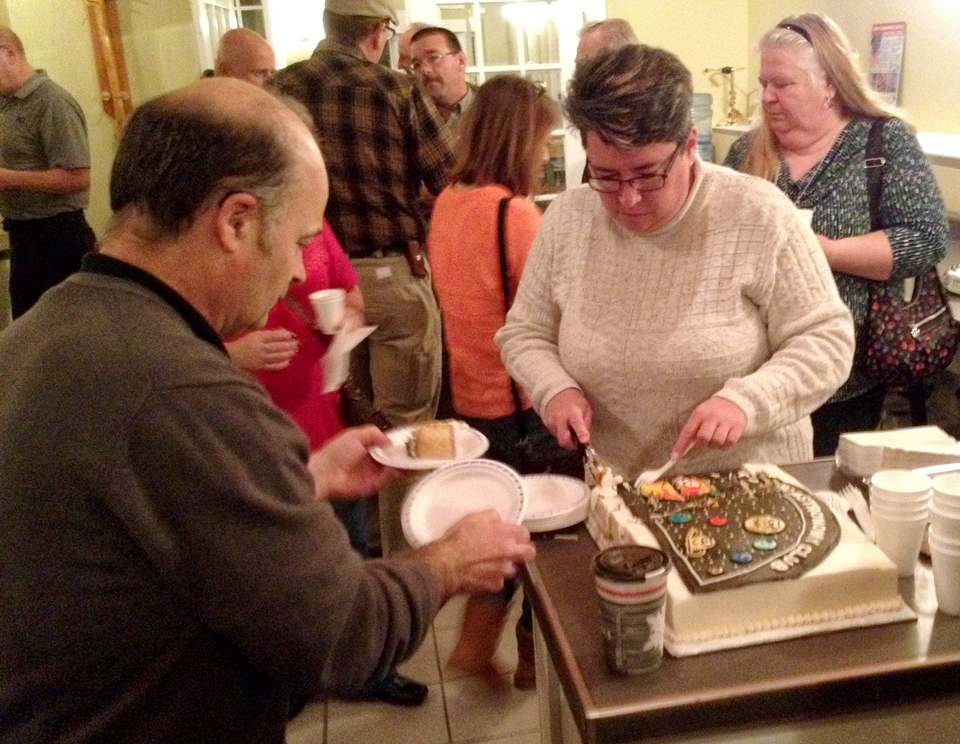 Paul Owen helps serve the cake provided by Trudy Almon at the last free astronomy course series on Nov. 28, 2017.