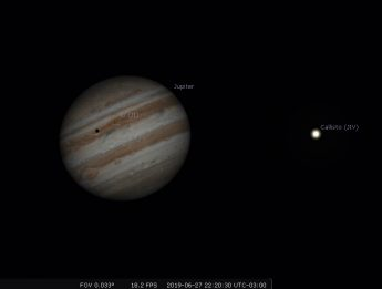 Photo of the planet Jupiter with the shadow of the moon lo crossing over the surface.